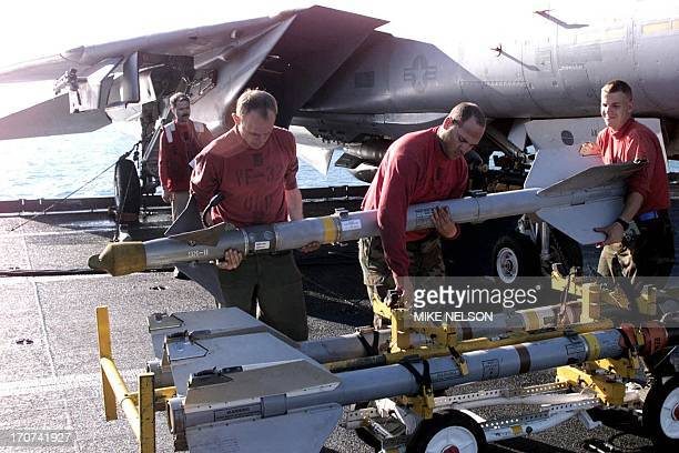 US Navy airmen from the USS Enterprise take off a rocket from an F14 Tomcat 20 December following the fourday air and missile assault on Iraq The...