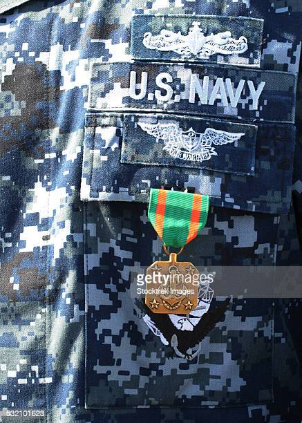 A Navy and Marine Corps Achievement Medal adorns the U.S. Navy uniform.