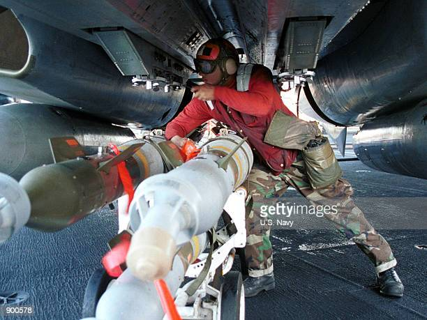 """Navy Aviation Ordnanceman applies attachments for a 500-pound laser-guided bomb onto a F-14D """"Tomcat"""" fighter November 7, 2001 aboard the USS Carl..."""