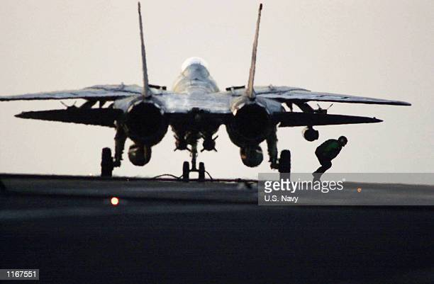 """Navy Aviation Ordnanceman runs out from beneath an F-14D """"Tomcat"""" after putting safety pins back into unexpended ordnance October 10, 2001 on the..."""