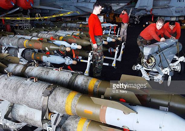 """Navy Aviation Ordnancemen move 1000-pound laser-guided bomb units and """"Maverick"""" missiles into for loading on to F/A-18 """"Hornet"""" strike fighters and..."""