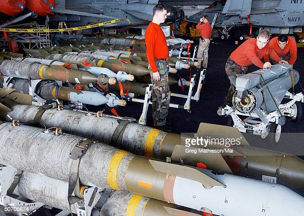 US Navy Aviation Ordnancemen moving 1000pound laserguided bomb units and Maverick missiles into for loading on to F/A18 Hornet strike fighters and...