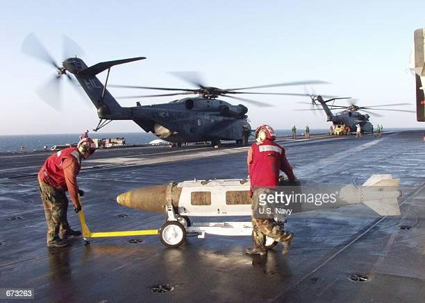 Navy Aviation Ordnancemen transport a Joint Direct Attack Munition across the flight deck November 21, 2001 aboard the USS Carl Vinson. The USS Carl...