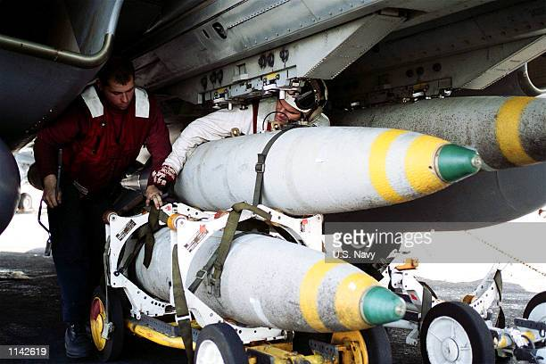 S Navy Aviation Ordnancemen work with MK83 bombs under the wing of a F14 Tomcats November 13 2001 while aboard the USS Theodore Roosevelt The USS...