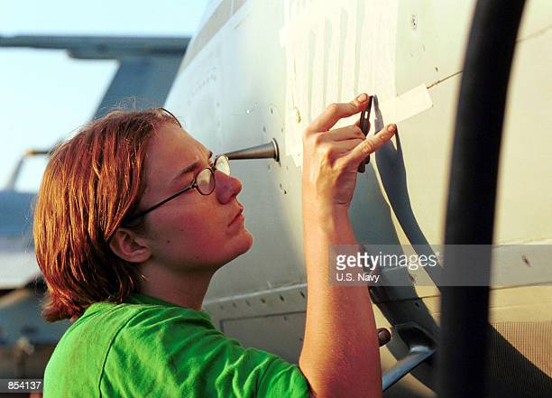"""Navy Aviation Structural Mechanic prepares a stencil for painting on the fuselage of an F/A-18 """"Hornet"""" while onboard the aircraft carrier USS Carl..."""