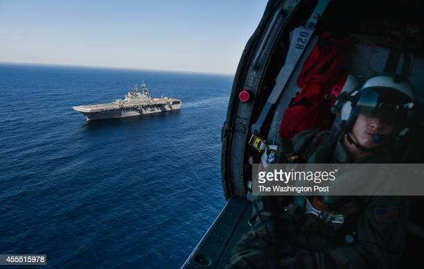 Navy AWS2 Steven Porter of Rosamond Ca is seen aboard an MH60S Seahawk helicopter prior to landing aboard the USS America on August 4 2014 in the...