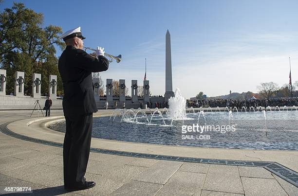 Navy Band bugler plays taps during a Veterans Day event at the World War II Memorial on the National Mall in Washington DC November 11 2014 AFP PHOTO...