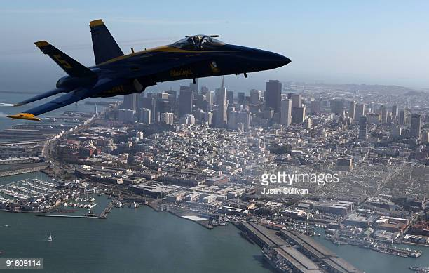 S Navy Blue Angels F/A18 Hornet piloted by US Marine Corps Major Nathan Miller flies past the San Francisco skyline during a practice flight ahead of...