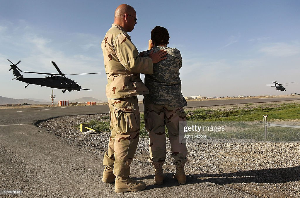 U.S. Navy Chaplain LCDR. Charles Hodges comforts CAPT. Patricia Hagan after the head nurse bid farewell to a young Afghan girl who was flown back to her rural village on a U.S. medevac helicopter on March 20, 2010 from the military hospital at Kandahar Airfield in southern Afghanistan. The child, Mina, 7, was critically ill with an abdominal infection when brought to the Role III Multinational Medical Unit for treatment. Medical personnel treat wounded soldiers, Taliban insurgent detainees and civilians alike. Severely wounded American and other international soldiers are treated and flown out for more advanced treatment outside of Afghanistan. Wounded and sick Afghan children often stay longer and medical staff, far from home and their own families, sometimes grows emotionally close to them.