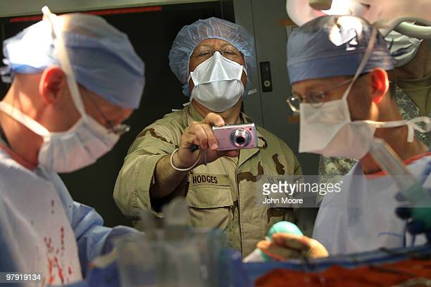 S Navy Chaplain LCDR Charles Hodges photographs as doctors perform brain surgery on an Afghan civilian on March 21 2010 at the military hospital at...