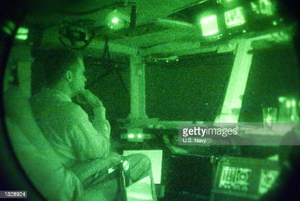 Navy commanding officer watches aircraft prepare for a second day of night strikes into Afghanistan in support of Operation Enduring Freedom October...