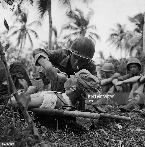 Navy corpsman gives a drink of water to an injured Marine, during the Battle of Guam, August 1944.
