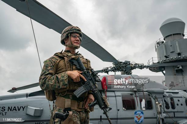 A navy crew member of the USS Blue Ridge stands guard on the deck in front of a Sikorsky SH60 Seahawk during a port call on April 20 2019 in Hong...