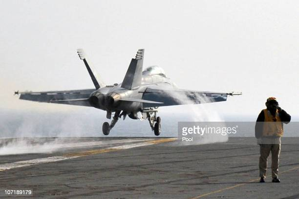 A US Navy crew member stands on deck as a F18 Super Hornet strike fighter plane takes off from the deck of USS George Washington during a joint US...