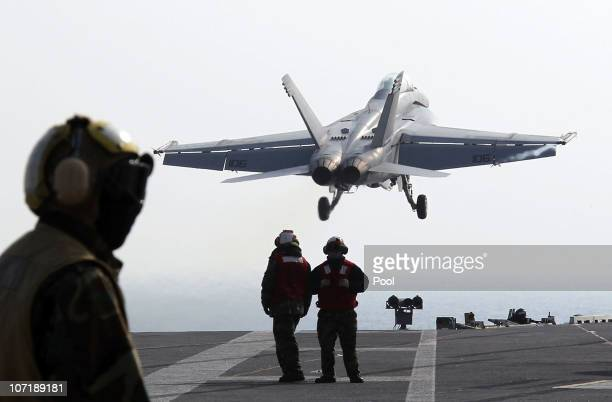 US Navy crew members stand on deck as a F18 Super Hornet strike fighter plane takes off from the deck of USS George Washington during a joint US and...