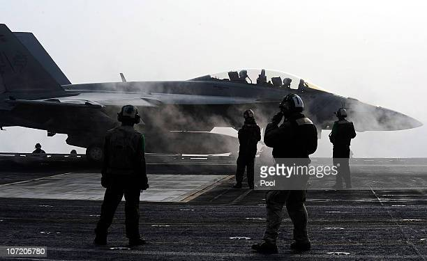 Navy crew members stand on deck as a F18 Super Hornet strike fighter plane takes off from the USS George Washington during a joint US and South Korea...