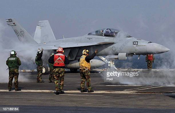 A US Navy crew members work on deck as a F18 Super Hornet strike fighter plane takes off from the deck of USS George Washington during a joint US and...