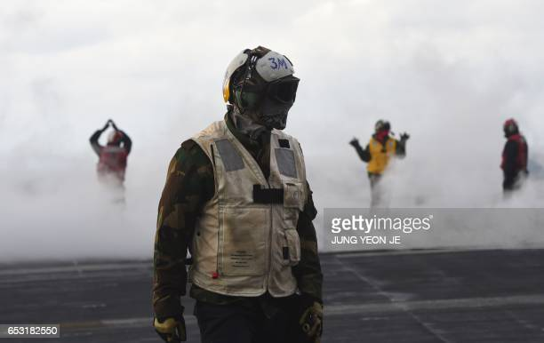 Navy crew members work on the deck of the Nimitzclass aircraft carrier USS Carl Vinson during a South KoreaUS joint military exercise in seas east of...