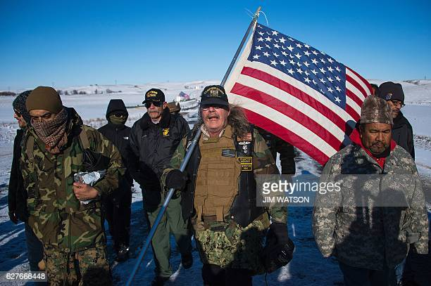US Navy deep sea diving veteran Rob McHaney holds an American flag as he leads a group of veteran activists back from a police barricade on a bridge...
