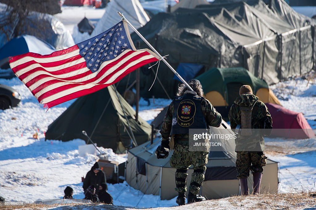 Navy deep sea diving veteran Rob McHaney (C) holds an American flag as he leads a group of veteran activists back from a police barricade on a bridge near Oceti Sakowin Camp on the edge of the Standing Rock Sioux Reservation on December 4, 2016 outside Cannon Ball, North Dakota. Native Americans and activists from around the country gather at the camp trying to halt the construction of the Dakota Access Pipeline. / AFP / JIM