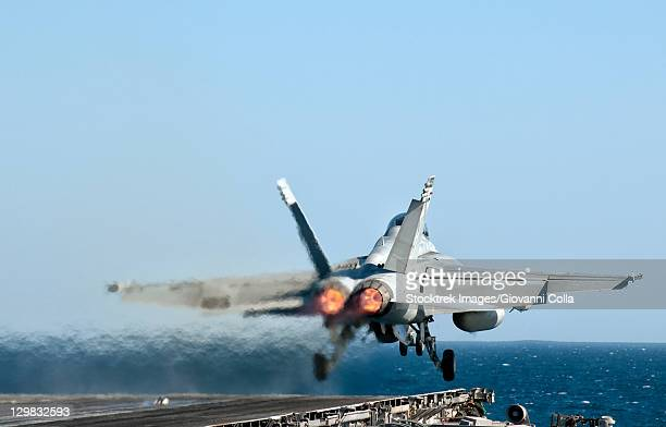 A US Navy F/A-18F Super Hornet launches from the flight deck of aircraft carrier USS Nimitz.