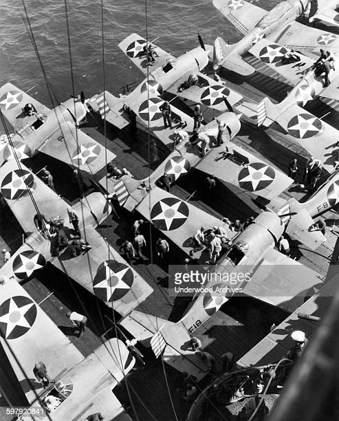 US Navy fighter planes recently returned from a raid on a Japanese held island get their armaments checked and reloaded by the aircraft carrier...