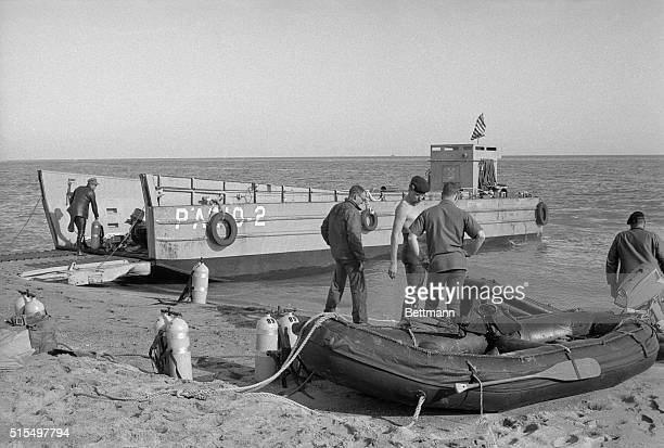US Navy frogmen stand on the beach recently preparing to search for a missing nuclear bomb which is believed to be lying in 200 fathoms of water off...