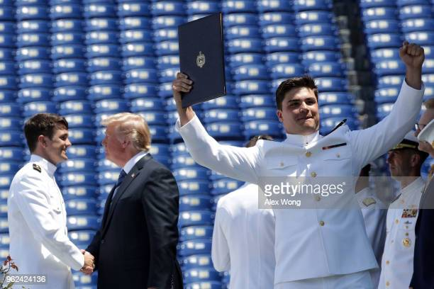 S Navy graduate celebrates after he received his diploma as US President shakes hands with another graduate during a graduation ceremony at the...