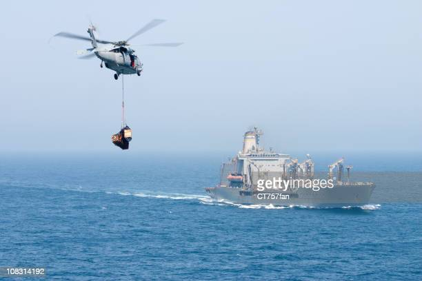 Navy helicopter delivering goods to ship