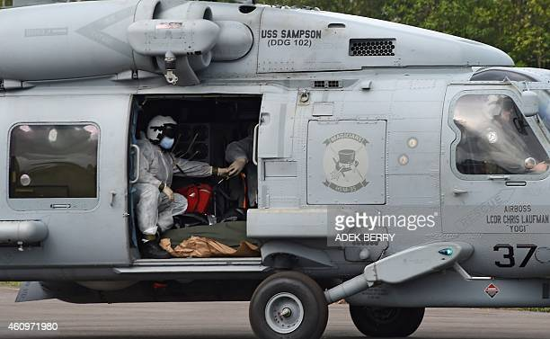 Navy helicopter from the USS Samson arrives to deliver a second batch of victims from AirAsia flight QZ8501 lost over the Java Sea on December 28 to...