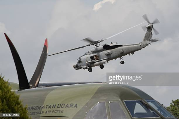 Navy helicopter from the USS Samson takes off over Indonesian aircraft after handing over four victims from AirAsia flight QZ8501 lost over the Java...