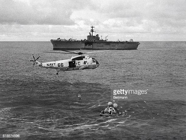 A Navy helicopter hovers over the Apollo 13 capsule in the Pacific Ocean as frogmen release the astronauts The USS Iwo Jima recovery vessel waits...