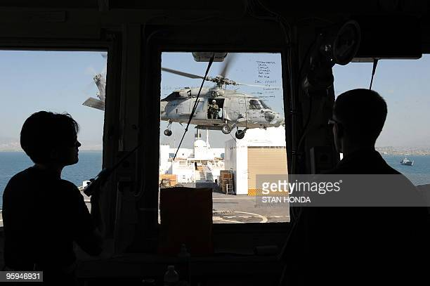 Navy helicopter prepares to land aboard the USNS Comfort hospital ship as seen from the flight control deck on 22 January 2010 in the harbor off...