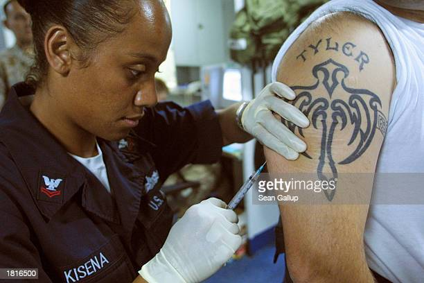 S Navy HM3 Angelita Kisena of Compton California administers an anthrax vaccine to a crew member aboard the USS Mount Whitney February 26 2003 in the...