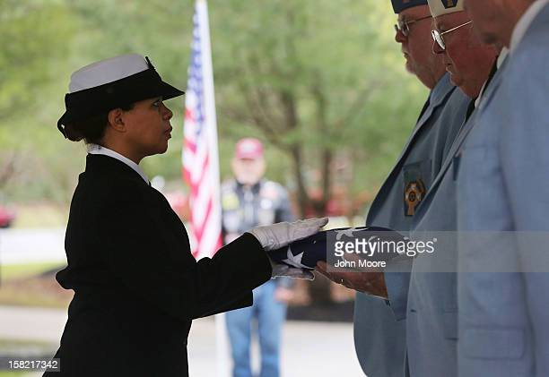 S Navy honor guard delivers a folded American flag following a service for Hurricane Sandy victim David Maxwell at the Calverton National Cemetery on...