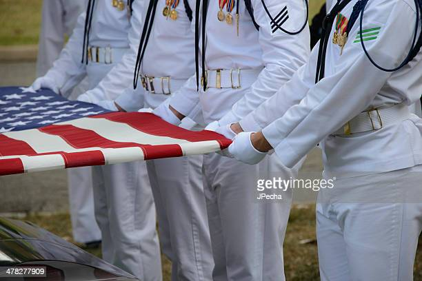 US Navy Honor guard holding American Flag over Casket