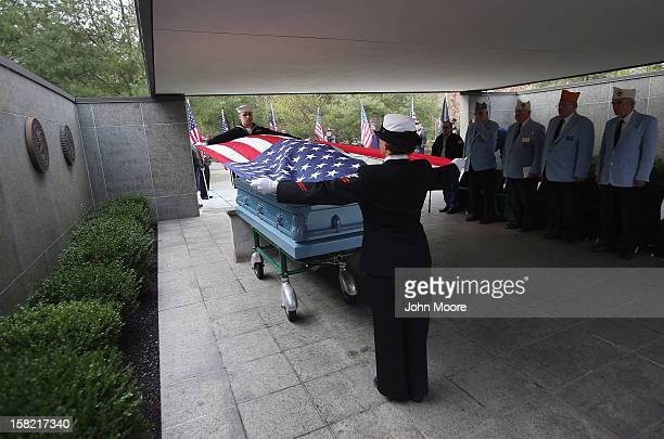 S Navy honor guard removes an American flag from the casket of Hurricane Sandy victim David Maxwell before his burial at the Calverton National...