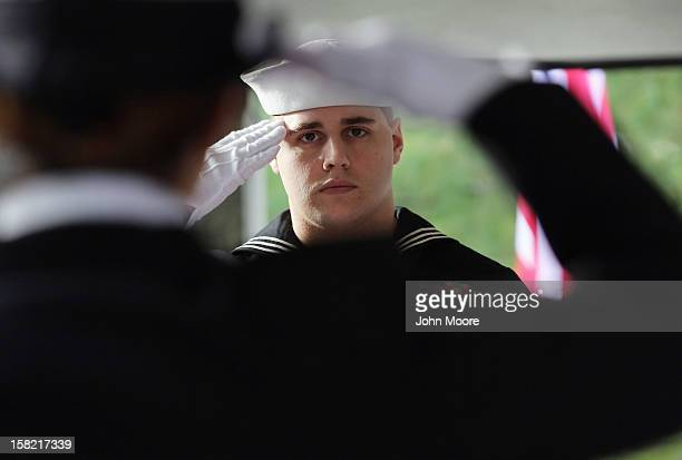 S Navy honor guard salutes over the casket of Navy veteran David Maxwell before his burial at the Calverton National Cemetery on December 11 2012...