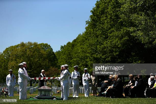 S Navy honor guard team holds an American flag over a casket with the remains of four sailors missing since a helicopter crash during the Vietnam War...