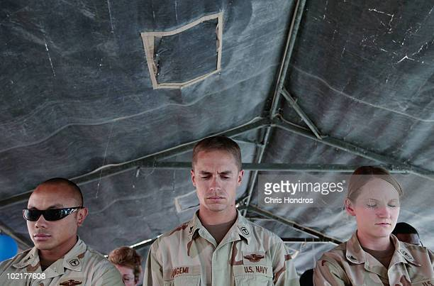 S Navy Hospital Corpsmen Joshua Saniel William Cangemi and Jessica Hall bow their heads in prayer before a ceremony to mark their organization's...