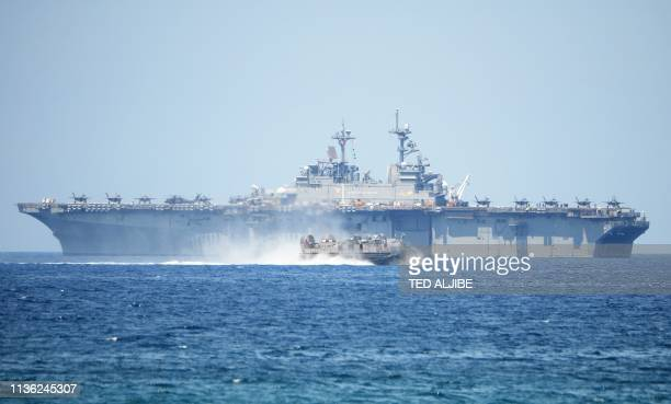 Navy hover craft speeds past the USS Wasp US Navy multipurpose amphibious assault ship during the amphibious landing exercises as part of the annual...