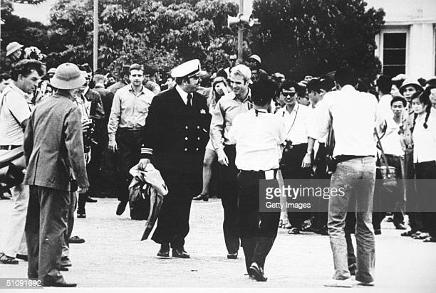 US Navy Lt Cmdr Jay Coupe Center Left Escorts Lt Cmdr John Mccain To A Waiting US Air Force C141A Starlifter Cargo Transport Aircraft At Gia Lam...