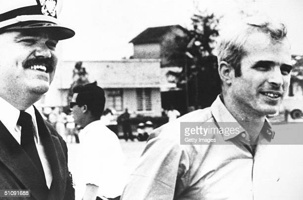 US Navy Lt Cmdr Jay Coupe Left Escorts Lt Cmdr John Mccain To A Waiting US Air Force C141A Starlifter Cargo Transport Aircraft At Gia Lam Airport...