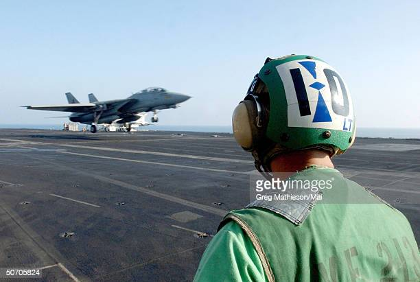 US Navy Lt Jeff Wood Tactical Aerial Reconnaissance Pod System Officer from the Black Lions of Fighter Squadron Two One Three waits for an F14 Tomcat...