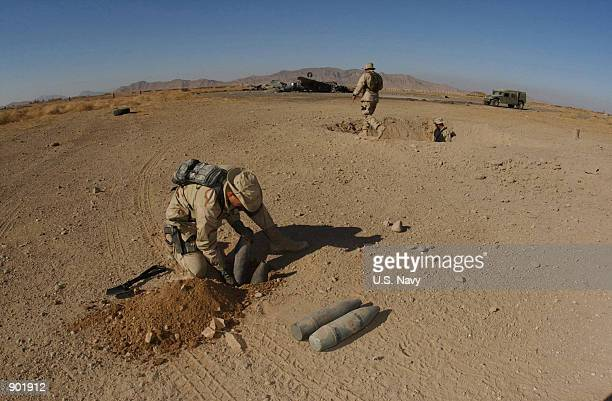 S Navy Lt Mike Runkle of Virginia Beach Va assigned to Explosive Ordnance Disposal Mobile Unit Two Detachment18 prepares charges to blow up...