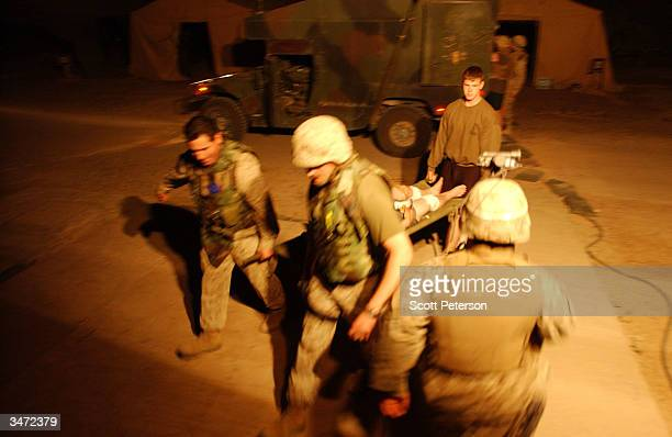 Navy medical corpsmen carry in a patient as they treat US Marines with bullet wounds inflicted during an ambush by Iraqi insurgents east of the...