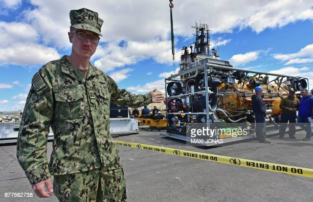 Navy member walks by the Pressurized Rescue Module #PRM which will take part in the search and rescue of missing submarine ARA San Juan at the dock...