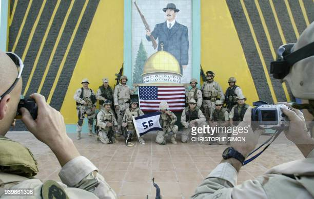 US navy members pose in front of a picture of Iraqi President Saddam Hussein at the entrance of the southern Iraqi town of Umm Qasr 06 April 2003 The...