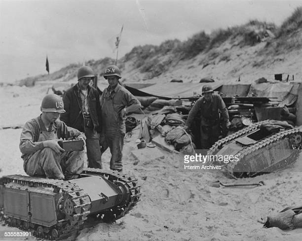 US Navy men look at a Goliath tracked mine on Normandy beach June 1944 The Goliath was a robot 'beetle' a remotely controlled explosive carrying...