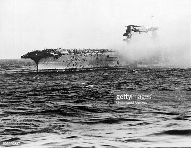US Navy men swarm down ropes over the side of the aircraft carrier USS Lexington after the Captain gave the order to abandon ship after it was hit by...
